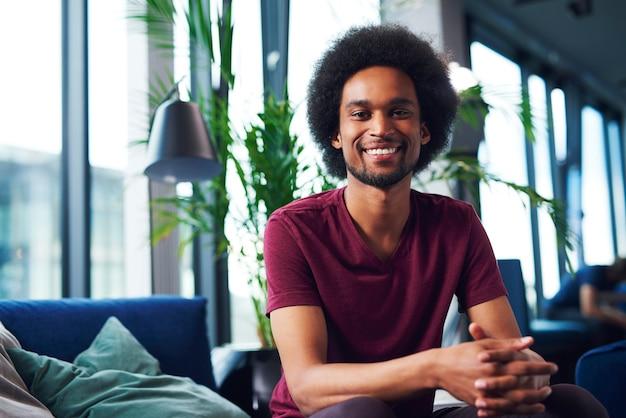 Portret van lachende afrikaanse man in woonkamer