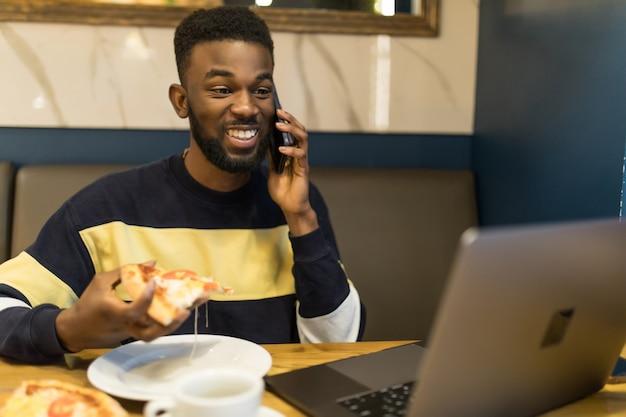 Portret van lachende afrikaanse man praten een mobiele telefoon zit in café met laptop en lunchen