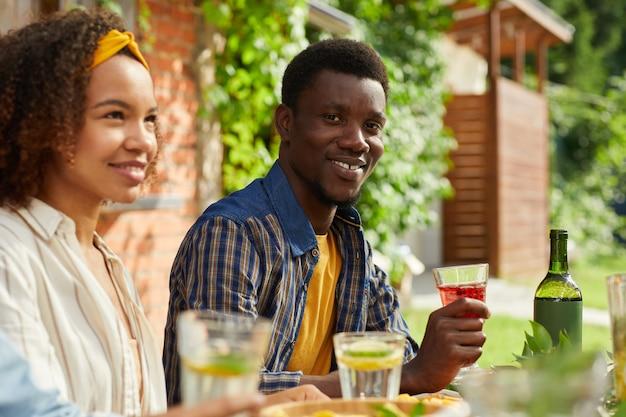 Portret van lachende afro-amerikaanse man genieten van diner met vrienden buiten zitten aan tafel tijdens zomerfeest