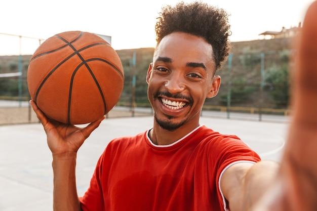 Portret van lachende afro-amerikaanse man met bal en selfie te nemen, tijdens het spelen van basketbal op de speelplaats buiten