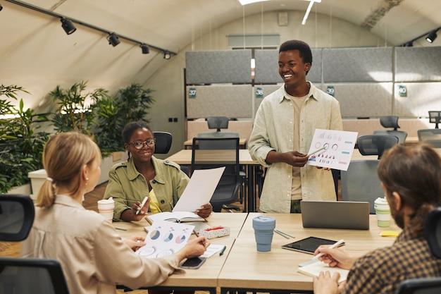 Portret van lachende afro-amerikaanse man met gegevensgrafiek terwijl het geven van verslag van statistieken en prestaties tijdens zakelijke bijeenkomst in moderne kantoor, kopieer ruimte