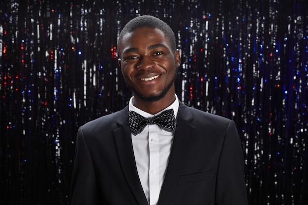 Portret van lachende afro-amerikaanse man met tux poseren op feestje tegen sprkling achtergrond, kopieer ruimte