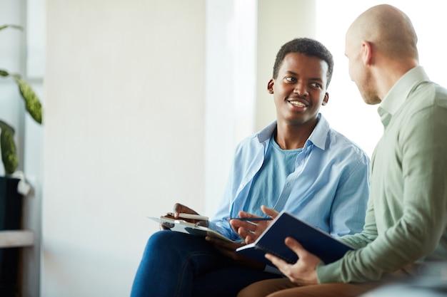 Portret van lachende afro-amerikaanse man praten met manager tijdens zakelijke stage in kantoor, kopieer ruimte