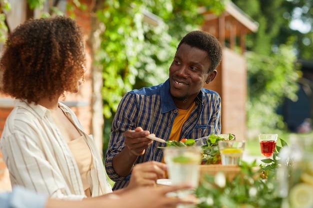 Portret van lachende afro-amerikaanse man vriendin kijken terwijl u geniet van een diner met vrienden en familie buiten op zomerfeest
