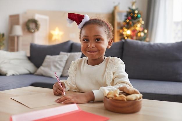 Portret van lachende afro-amerikaanse meisje brief schrijven aan de kerstman zittend aan tafel in gezellige woonkamer met kerstboom op achtergrond, kopieer ruimte