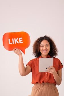Portret van lachende afro-amerikaanse meisje met krullend haar met behulp van digitale tablet en wens post op sociale media