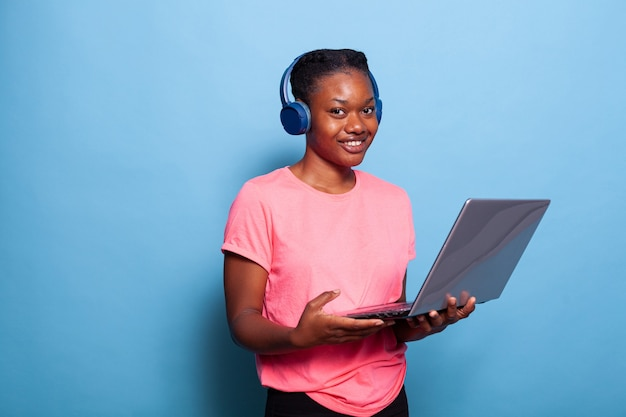 Portret van lachende afro-amerikaanse student met hoofdtelefoon die muziek luistert