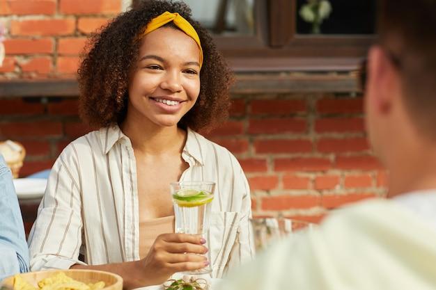 Portret van lachende afro-amerikaanse vrouw genieten van diner met vrienden buiten en verfrissende cocktail houden zittend aan tafel tijdens zomerfeest
