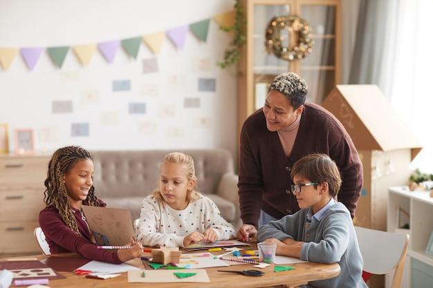 Portret van lachende afro-amerikaanse vrouw lesgeven kunst klasse met multi-etnische groep kinderen afbeeldingen tekenen op school