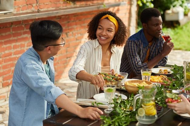 Portret van lachende afro-amerikaanse vrouw met aardappelschotel terwijl u geniet van een diner met vrienden en familie buiten op zomerfeest