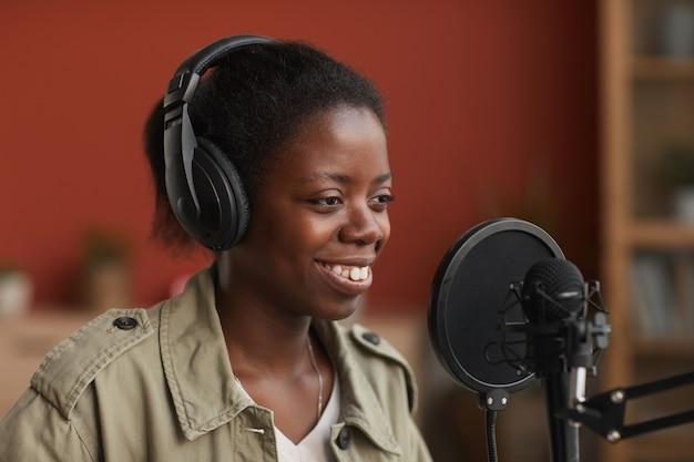 Portret van lachende afro-amerikaanse vrouw zingen naar microfoon en hoofdtelefoon dragen tijdens het opnemen van muziek in de studio, kopieer ruimte