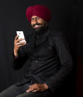 Portret van lachende authentieke inheemse indiase punjabi sikh mannen in tulband met borstelige baard, praten op mobiel