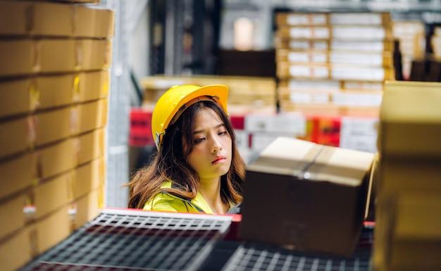 Portret van lachende aziatische ingenieur in helm vrouw bestel details en het controleren van goederen en benodigdheden op planken met goederen achtergrond in magazijn. logistieke en zakelijke export
