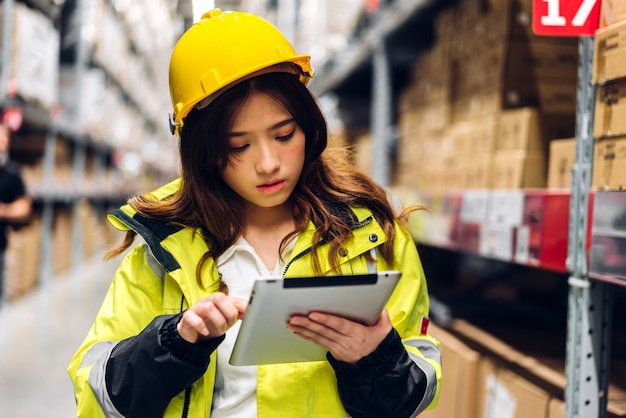 Portret van lachende aziatische ingenieur in helmen vrouw order details op tabletcomputer voor het controleren van goederen en benodigdheden op planken met goederen achtergrond in magazijn. logistieke en zakelijke export