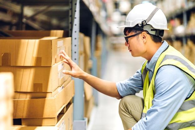 Portret van lachende aziatische ingenieur voorman in helmen man bestellen details controleren van goederen en leveringen op planken