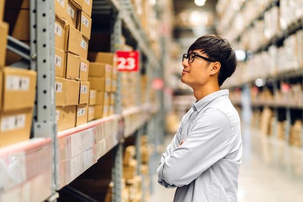 Portret van lachende aziatische manager werknemer man permanent en bestel details controleren goederen en benodigdheden op planken met goederen achtergrond in magazijn. logistieke en zakelijke export