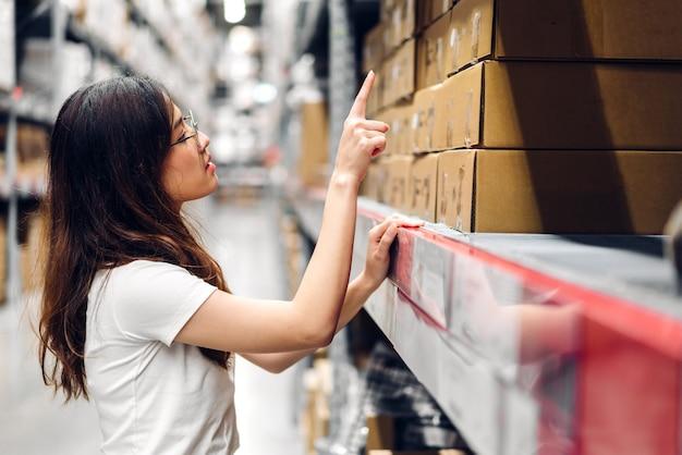 Portret van lachende aziatische manager werknemer vrouw die staat en bestelt op kartonnen doos in magazijn