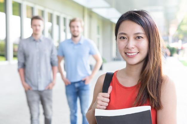 Portret van lachende aziatische vrouwelijke student met boek