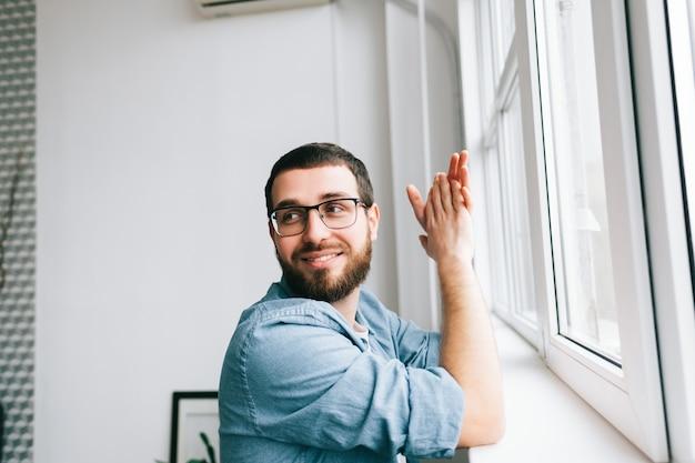 Portret van lachende blanke man die in de buurt van venster in lichte kamer.
