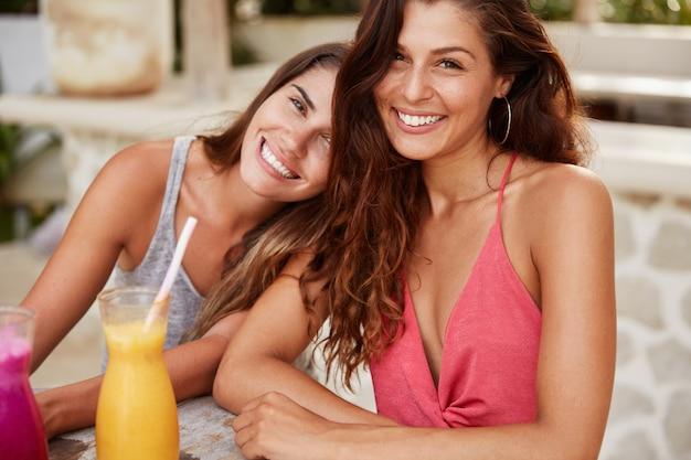 Portret van lachende blije vrouw met positieve glimlach zit in de buurt van haar vriendin die naar de schouder leunt, geniet van saamhorigheid en veel plezier