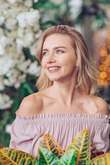 Portret van lachende blonde jonge vrouw wegkijken
