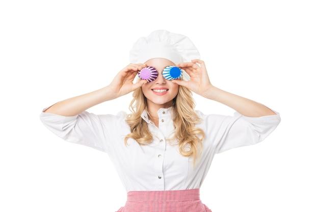 Portret van lachende blonde vrouw die betrekking hebben op ogen met cupcake bakken vormen. studio shot.isolated.