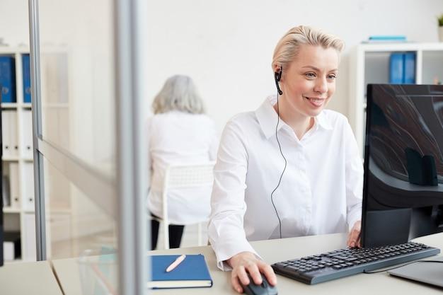 Portret van lachende blonde vrouw praten met microfoon tijdens het gebruik van computer in kantoor interieur, klantenondersteuning en callcenter concept