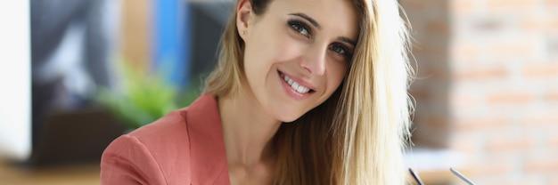 Portret van lachende blonde zakenvrouw op de werkplek