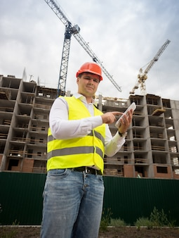 Portret van lachende bouwingenieur poseren met digitale tablet