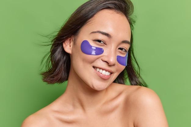 Portret van lachende brunette aziatische vrouw met natuurlijke schoonheid brengt blauwe hydrogelpleisters onder de ogen aan