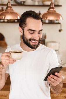 Portret van lachende brunette man die koffie drinkt en smartphone gebruikt terwijl hij thuis ontbijt in een stijlvolle keuken