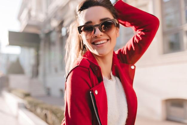 Portret van lachende brunette vrouw genieten van zonnige dag buiten