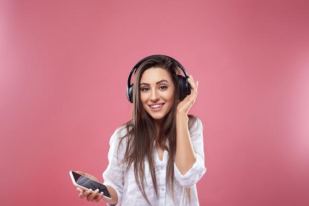 Portret van lachende brunette vrouw in hoofdtelefoons met smartphone luisteren muziek