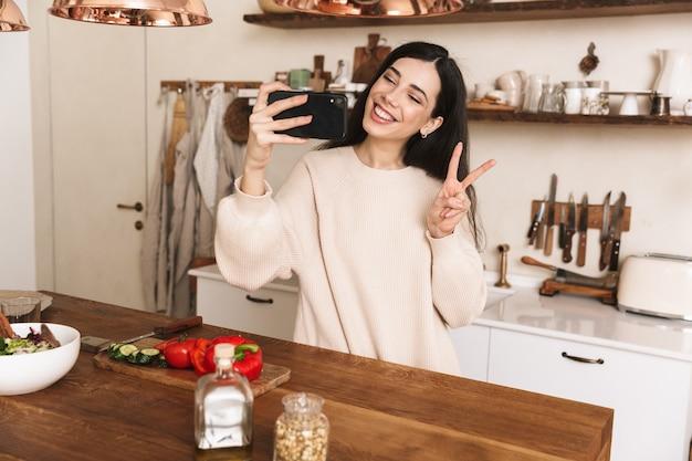 Portret van lachende brunette vrouw selfie foto nemen op smartphone tijdens het koken van groene salade met groenten in stijlvolle keuken thuis