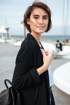 Portret van lachende charmante jonge vrouw met rugzak buiten wandelen