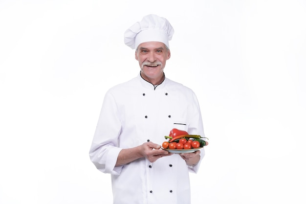 Portret van lachende chef-kok met een kom groente geïsoleerd op een witte muur