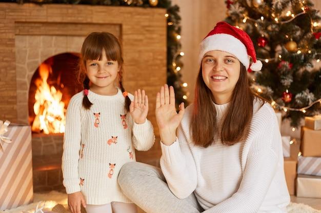 Portret van lachende donkerharige vrouw met witte trui en kerstman hoed poseren met haar dochtertje, camera kijken en handen zwaaien, merry christmas.