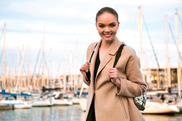 Portret van lachende elegante prachtige vrouw poseren in de buurt van luxe jachtclub, beige kasjmier jas en rugzak dragen, toerist, warme pastelkleuren.