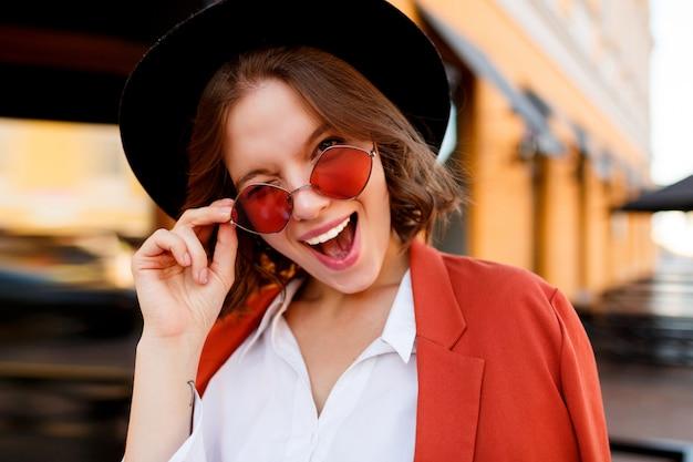 Portret van lachende europees meisje in schattige oranje zonnebril, jas en zwarte hoed. herfst mode. straat café.