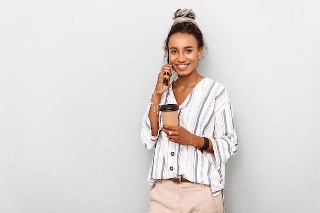 Portret van lachende gelukkig afrikaanse zakenvrouw met dreadlocks geïsoleerd op wit koffie drinken praten door de mobiele telefoon.