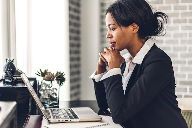 Portret van lachende gelukkig afro-amerikaanse zwarte vrouw ontspannen met behulp van technologie van laptopcomputer zittend op tafel