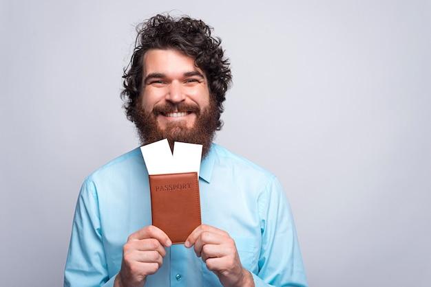 Portret van lachende gelukkig bebaarde man in casual bedrijf paspoort en vliegende kaartjes close-up