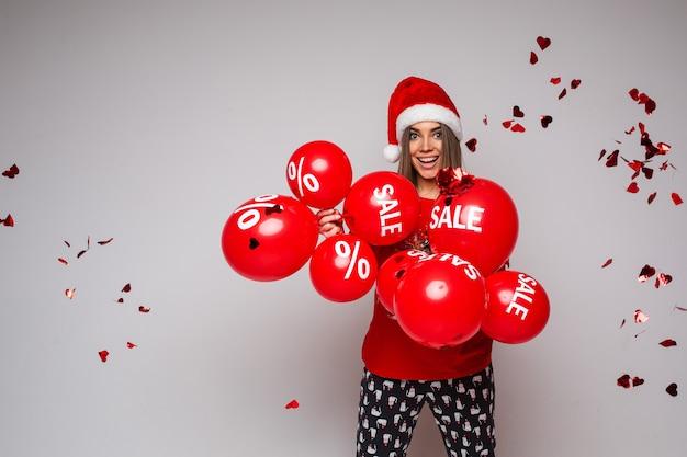 Portret van lachende gelukkig brunette in kerstmuts met bos rode ballonnen