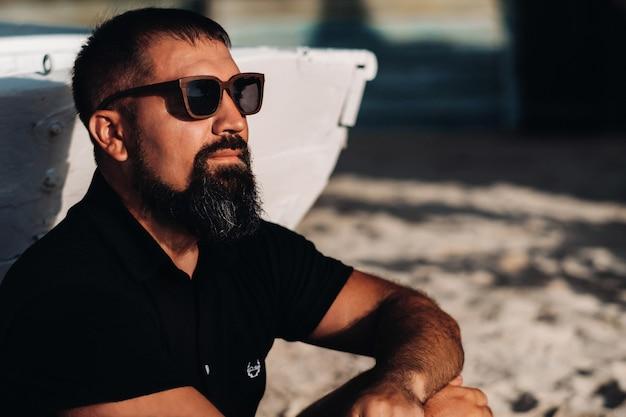 Portret van lachende gelukkig knappe sexy man weergegeven: gespierd fit lichaam genieten en ontspannen staande op het tropische strand en kijken naar camara. zomervakanties en reizen.