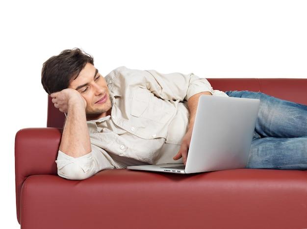 Portret van lachende gelukkig man met laptop op divan, geïsoleerd op wit.