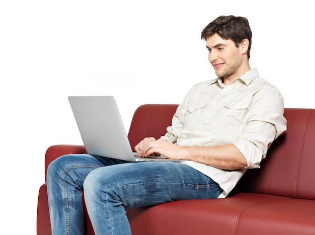 Portret van lachende gelukkig man met laptop zit op divan, geïsoleerd op wit.
