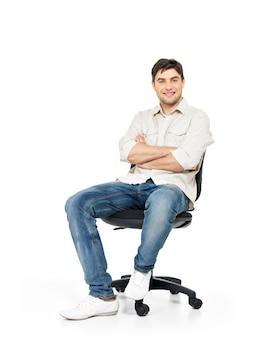 Portret van lachende gelukkig man zit op de bureaustoel op wit wordt geïsoleerd.