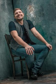 Portret van lachende gelukkig man zittend op de houten stoel op grijze studio