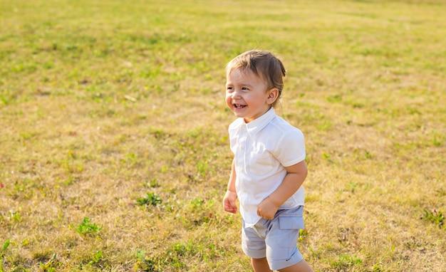 Portret van lachende gelukkige babyjongen op natuurlijke achtergrond in de zomer.