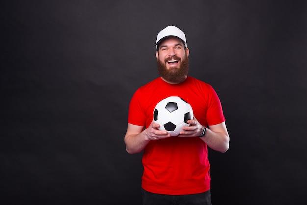 Portret van lachende gelukkige jonge man met voetbal en camera te kijken